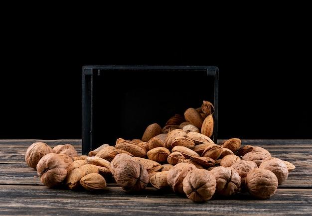 Vue latérale noix et amandes du panier noir sur horizontal en bois