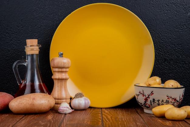 Vue latérale de nouvelles pommes de terre dans un bol avec du rouge et du blanc, du sel d'ail au beurre fondu et une assiette vide sur une surface en bois et une surface noire