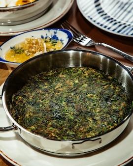 Vue latérale des oeufs au plat traditionnels azerbaïdjanais avec des herbes kuku dans la casserole