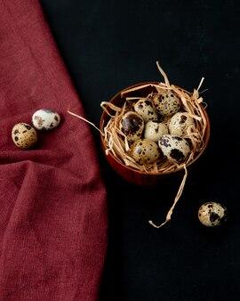 Vue latérale des œufs avec nid dans un bol sur fond bordeaux et noir avec copie espace