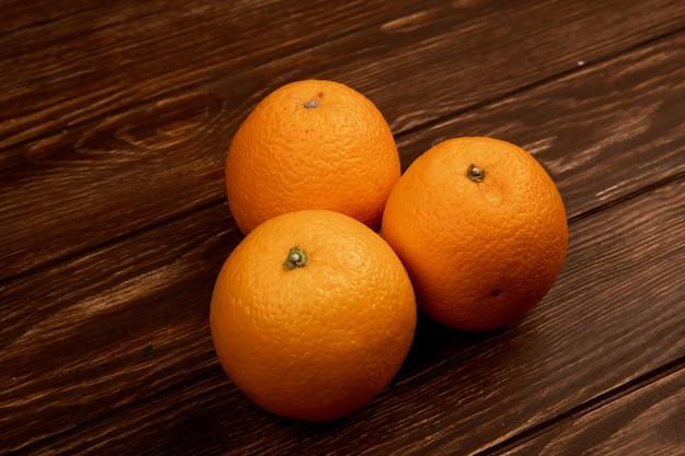 Vue latérale d'oranges mûres fraîches isolé sur une surface en bois