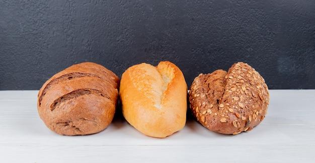 Vue latérale des pains comme des pains vietnamiens noir et blanc ensemencés et du pain noir sur une surface en bois et une surface noire avec copie espace