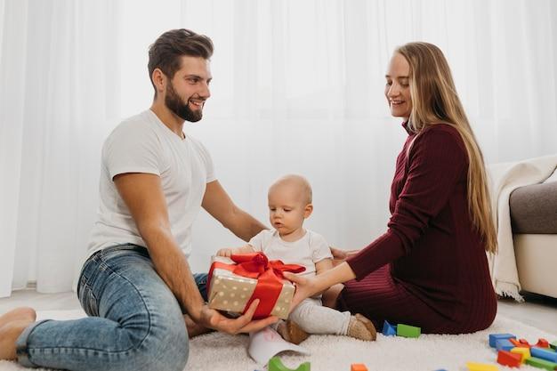 Vue latérale des parents à la maison avec leur bébé et cadeau