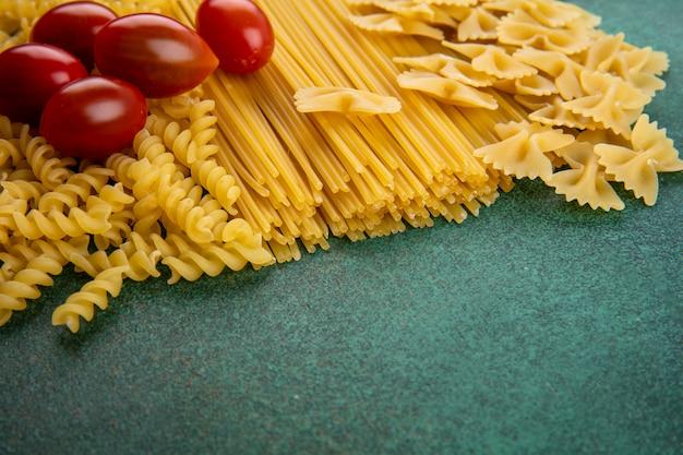 Vue latérale des pâtes crues avec des spaghettis crus et des tomates cerises sur une surface verte