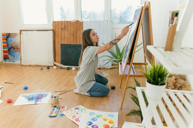 Vue latérale de la peinture féminine et de son travail