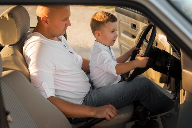 Vue latérale père et enfant en voiture