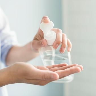 Vue latérale d'une personne utilisant un désinfectant pour les mains