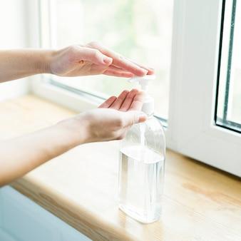 Vue latérale d'une personne utilisant un gel antibactérien