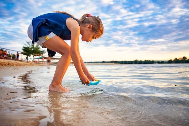 Vue latérale de la petite belle fille de race blanche jouant avec de minuscules canards jaunes en caoutchouc dans la petite piscine bleue, debout sur le sable de la plage