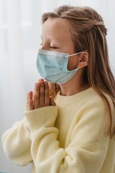 Vue latérale de la petite fille priant avec un masque médical