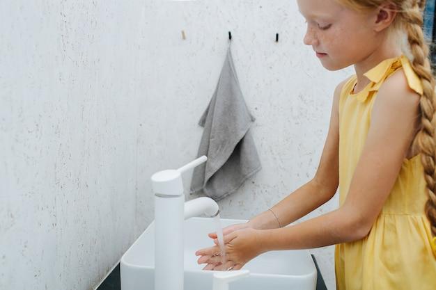Vue latérale d'une petite fille se lavant les mains dans le lavabo de la salle de bain