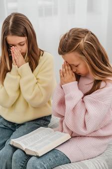 Vue latérale des petites filles priant