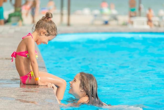 Vue latérale petites soeurs filles nagent dans la piscine