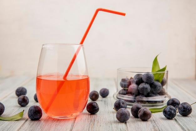 Vue latérale des petits prunelles bleu-noir aigre sur un bol en verre avec du jus sur un verre avec prunelles isolé sur un fond de bois gris