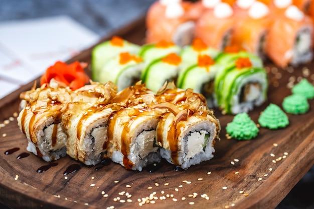 Vue latérale philadelphia roll avec anguille de conger fromage à la crème peau de saumon séchée sauce teriyaki graines de sésame et wasabi sur une planche