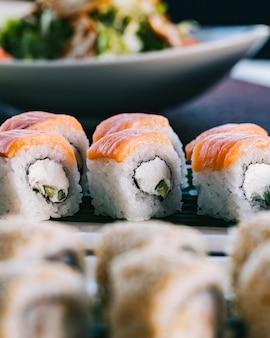 Vue latérale philadelphia roll fromage à la crème concombre nori avec saumon