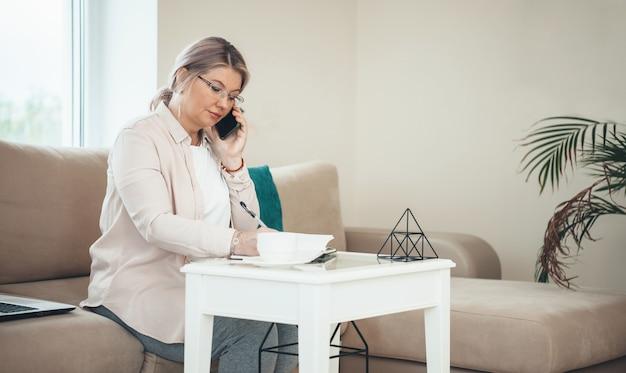 Vue latérale photo d'une femme d'affaires senior parlant au téléphone