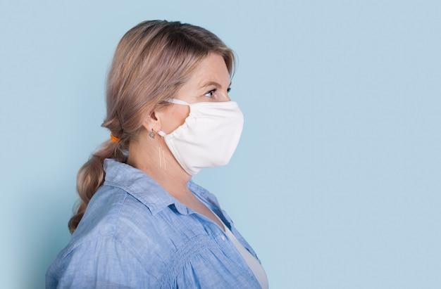 Vue latérale photo d'une femme de race blanche aux cheveux blonds portant un masque médical sur fond bleu avec espace libre