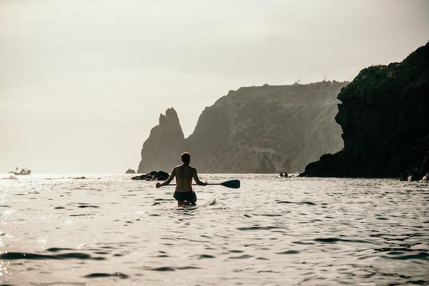 Vue latérale photo d'un homme nageant et se relaxant sur le sup board homme sportif dans la mer sur le stand