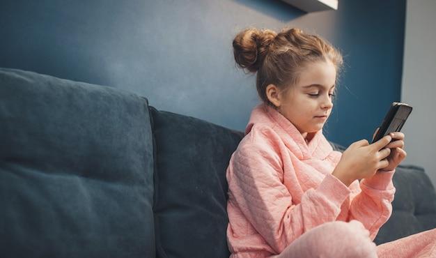 Vue latérale photo d'une jolie fille en vêtements roses discutant sur mobile assis sur un canapé près de l'espace libre
