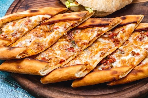 Vue latérale pide avec du fromage de viande hachée poivron vert chaud et tomate sur une planche