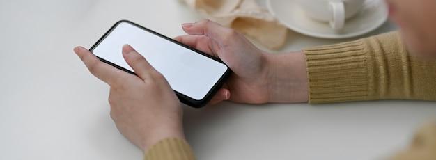 Vue latérale d'une pigiste à l'aide d'une maquette de smartphone pour contacter le client