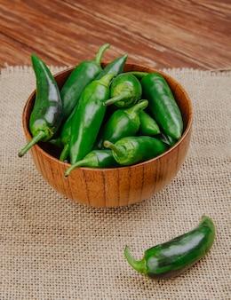 Vue latérale des piments verts frais dans un bol en bois sur un sac sur une surface rustique