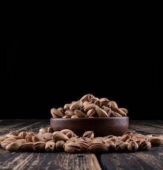 Vue latérale des pistaches dans un bol sur dark