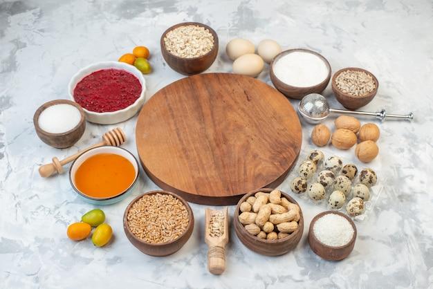 Vue latérale d'une planche de bois ronde parmi la confiture de farine fruits secs kumquats frais oeufs riz brun sur fond de glace