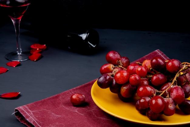 Vue latérale de la plaque avec raisin sur tissu avec verre et bouteille de vin rouge avec des pétales de fleurs sur fond noir