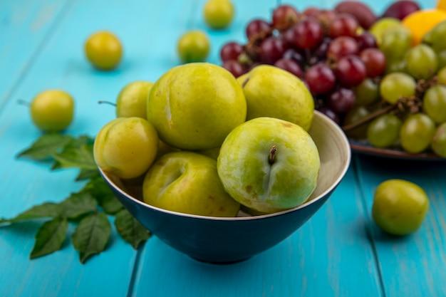 Vue latérale des pluots verts dans un bol avec assiette de raisins prunes nectacot sur fond bleu décoré de feuilles