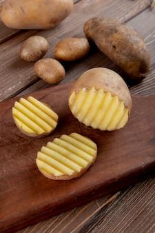 Vue latérale de la pomme de terre en tranches et coupées sur une surface en bois avec des pommes de terre entières sur fond de bois