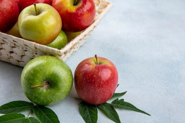 Vue latérale des pommes colorées dans un panier avec des branches de feuilles sur fond gris