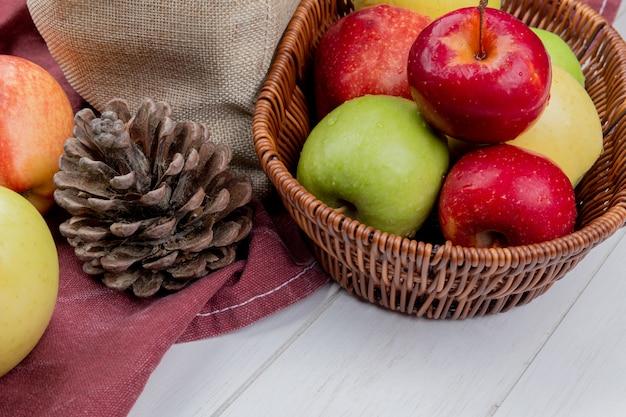 Vue latérale des pommes dans le panier avec pomme de pin et pommes sur tissu bordo et surface en bois