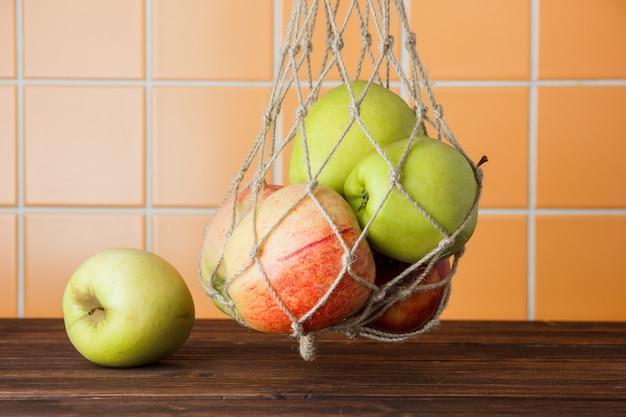 Vue latérale des pommes suspendues dans un sac net sur fond de carreaux en bois et orange. horizontal