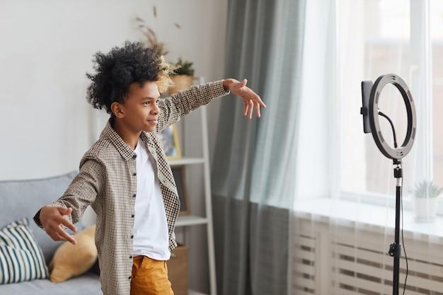 Vue latérale portrait d'un adolescent afro-américain filmant des vidéos à la maison et dansant devant la caméra sur un éclairage annulaire, concept de jeune blogueur, espace de copie