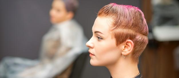 Vue latérale portrait d'une belle jeune femme de race blanche avec une courte coupe de cheveux rose en attente d'un coiffeur dans un salon de beauté