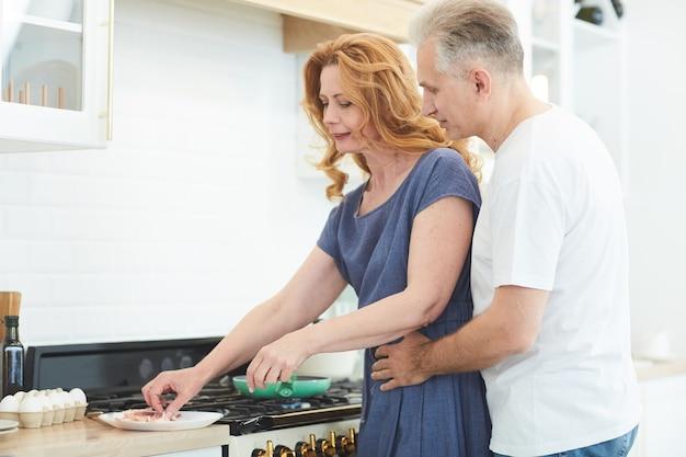 Vue latérale portrait de couple d'âge mûr cuisiner ensemble dans la cuisine à domicile avec l'homme embrassant la femme par derrière, copiez l'espace