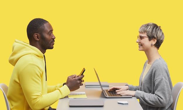 Vue latérale portrait de deux hommes d'affaires contemporains assis l'un en face de l'autre au bureau pendant la réunion et souriant sur fond jaune