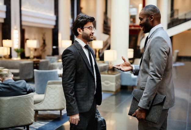 Vue latérale portrait de deux hommes d'affaires prospères discutant du travail tout en se tenant dans le hall de l'hôtel, espace pour copie