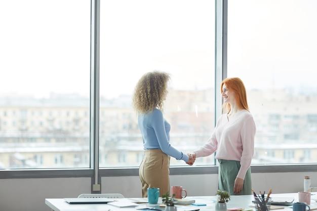 Vue latérale portrait de deux jeunes femmes d'affaires prospères se serrant la main après un entretien d'embauche ou une affaire en se tenant debout par fenêtre dans un bureau moderne, copiez l'espace