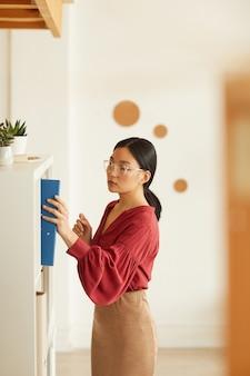 Vue latérale portrait de l'élégante femme d'affaires asiatique mettant le classeur à la bibliothèque contre le mur blanc au bureau, copiez l'espace