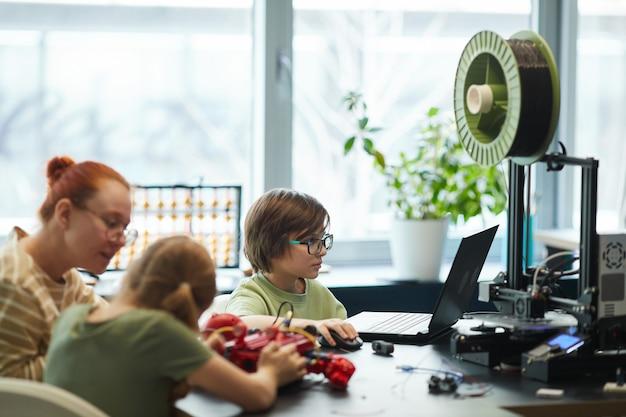 Vue latérale portrait d'enfants imprimant en 3d des pièces pour robots pendant la classe d'ingénierie à l'école moderne, espace de copie