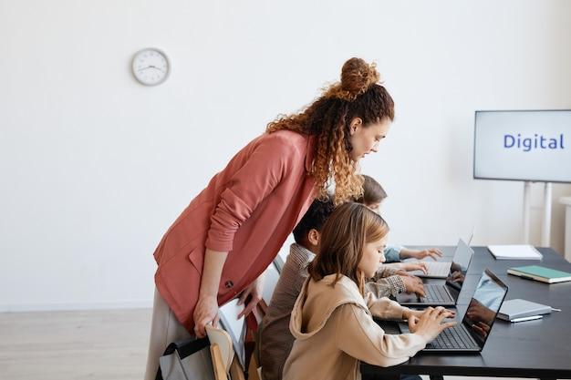 Vue latérale portrait d'une enseignante aidant les enfants à utiliser un ordinateur portable pendant les cours d'informatique à l'école, espace de copie