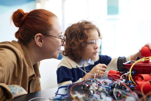Vue latérale portrait d'une enseignante aidant un garçon à construire un robot pendant la classe d'ingénierie à l'école