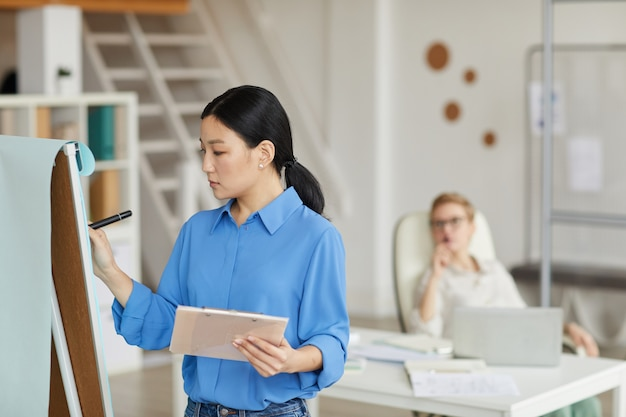 Vue latérale portrait de femme d'affaires asiatique écrit sur tableau blanc lors de la planification de projet au bureau, espace copie