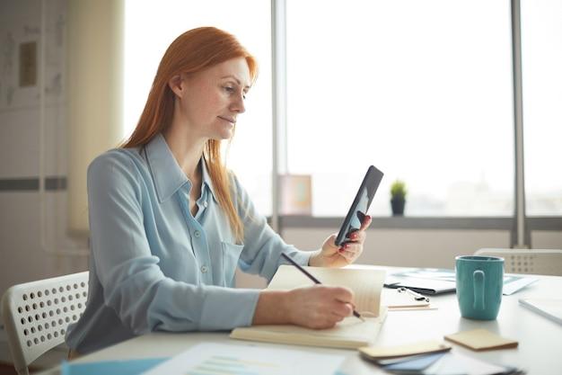 Vue latérale portrait de femme d'affaires aux cheveux rouges à l'aide de tablette numérique tout en prenant des notes dans le planificateur, la gestion du temps et le concept d'organisation, espace de copie