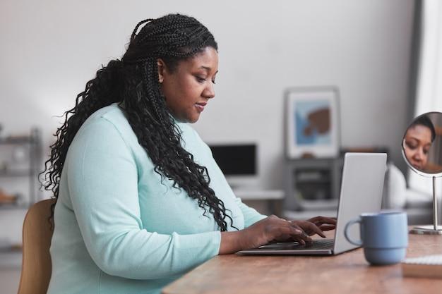 Vue latérale portrait d'une femme afro-américaine bien roulée utilisant un ordinateur portable au bureau et tapant tout en profitant du travail à domicile dans un intérieur minimal, espace de copie