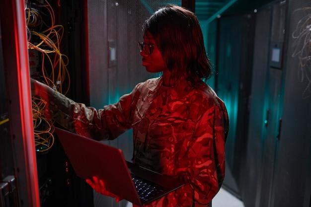 Vue latérale portrait d'une femme afro-américaine gérant un réseau informatique tout en travaillant avec un superordinateur dans la salle des serveurs éclairée par la lumière rouge, espace de copie