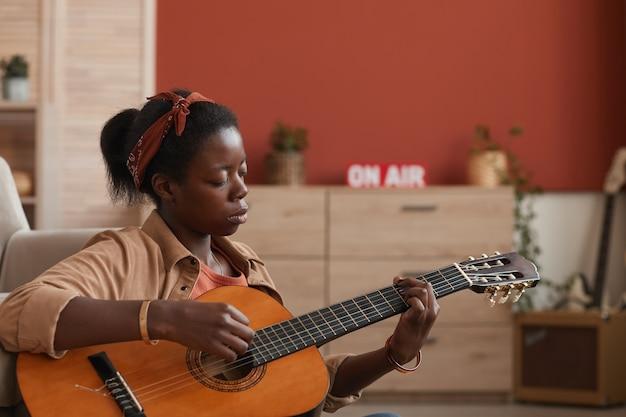 Vue latérale portrait de femme afro-américaine jouant de la guitare acoustique alors qu'il était assis sur le sol à la maison, copiez l'espace